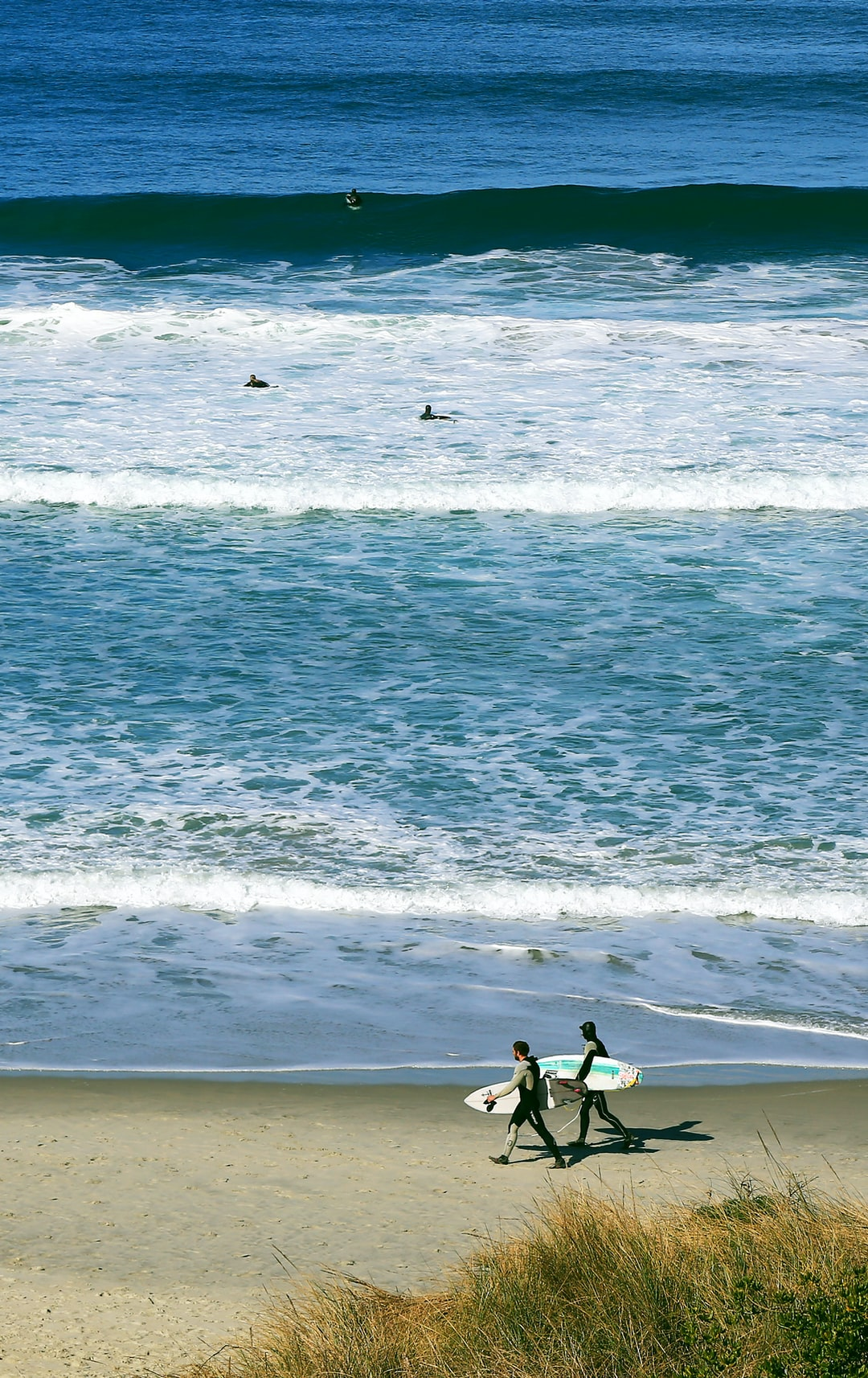 Surfies stride along next to the waves with their surfboards tucked under their arms.