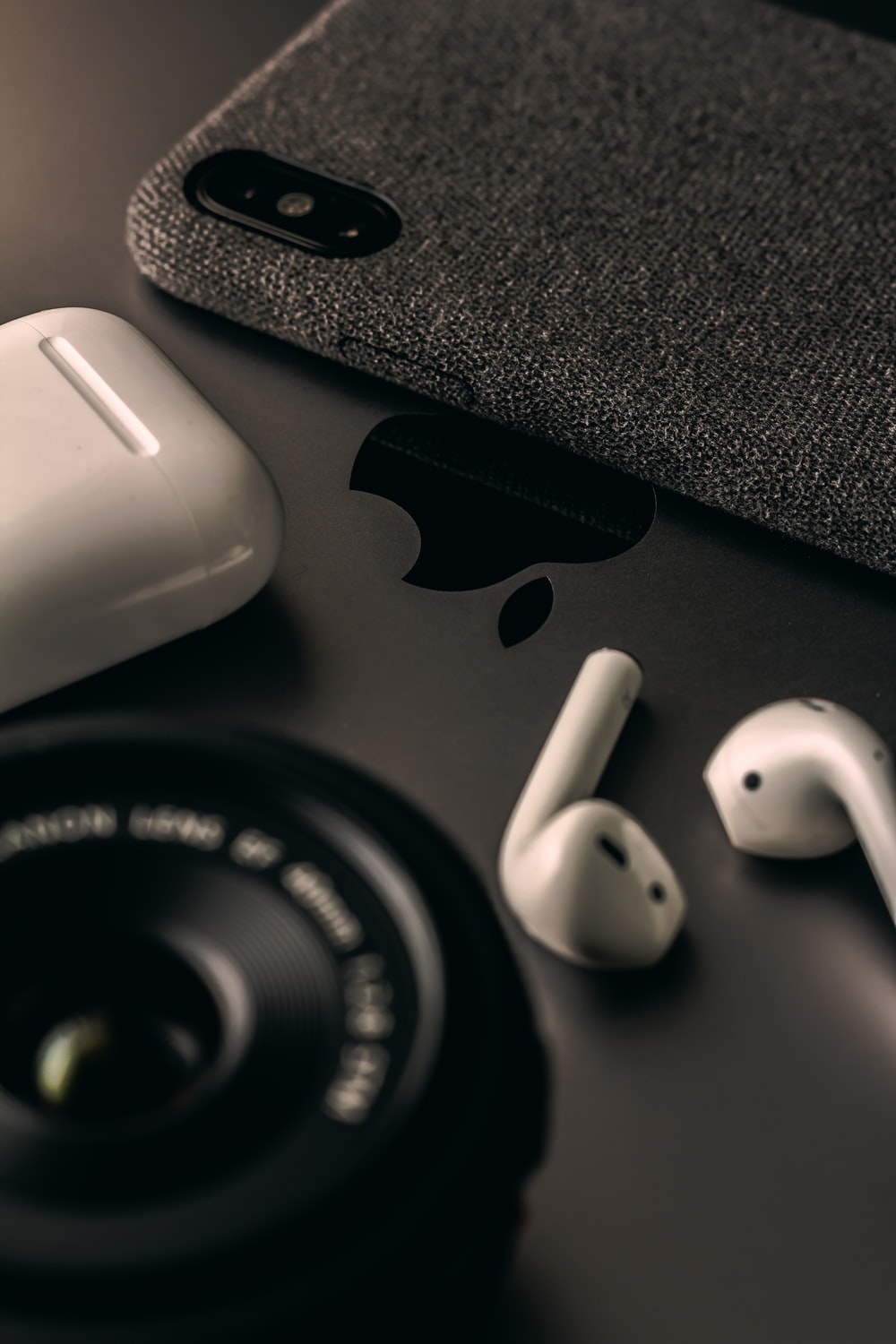 space gray iPhone X beside AirPods
