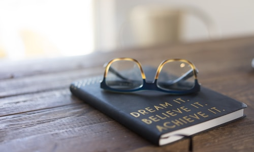 black and brown eyeglasses on book on brown wooden table