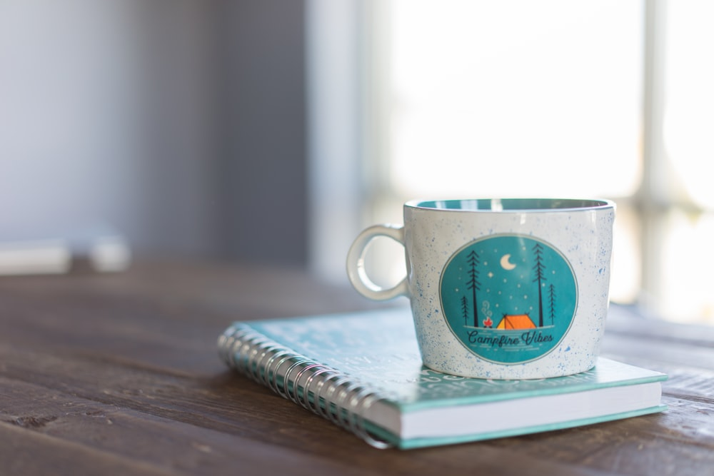white and blue ceramic mug on notebook