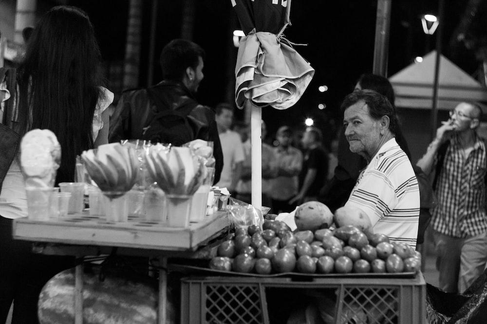 man sitting beside fruit stand