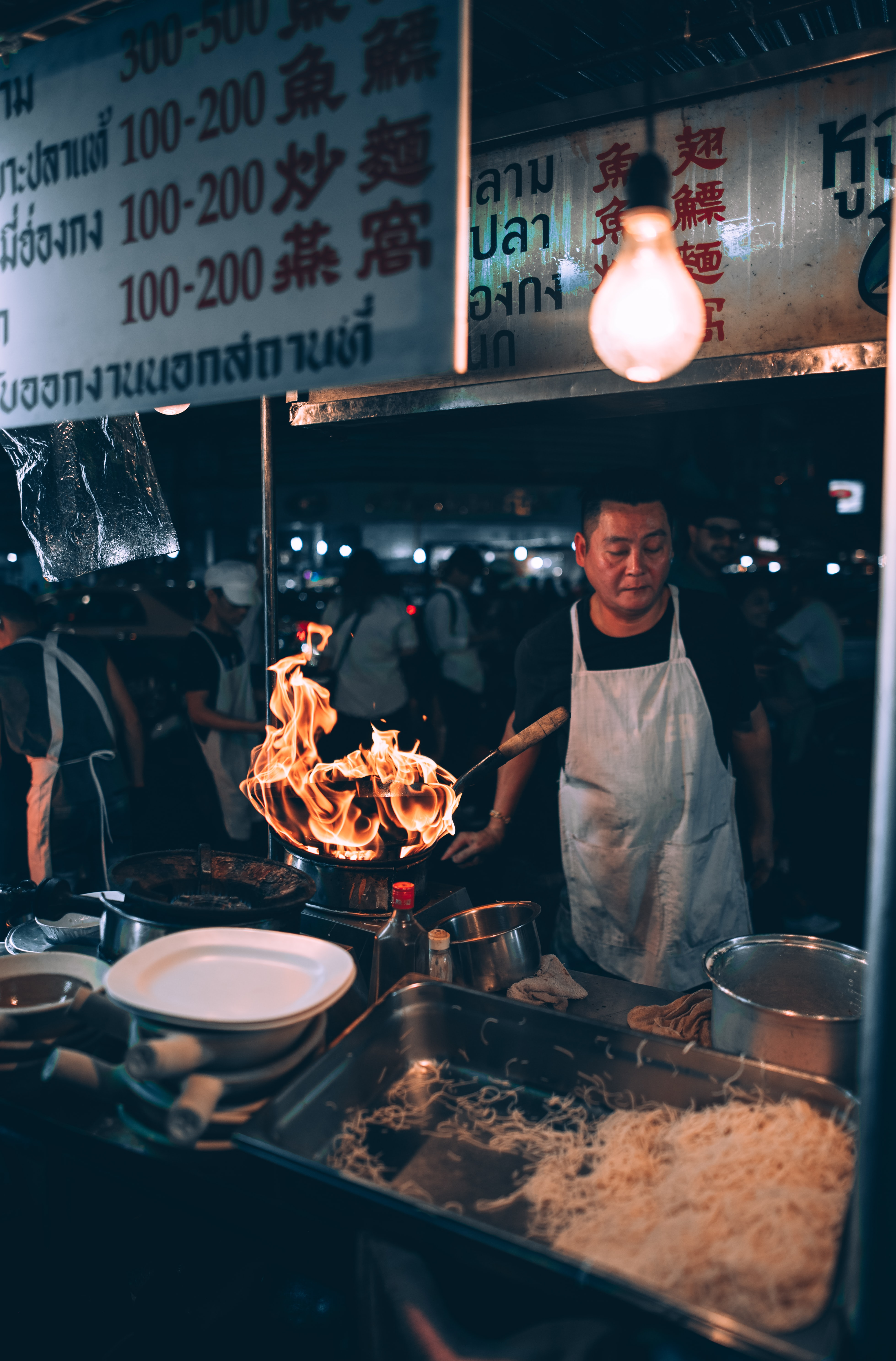 man cooking front of food stall