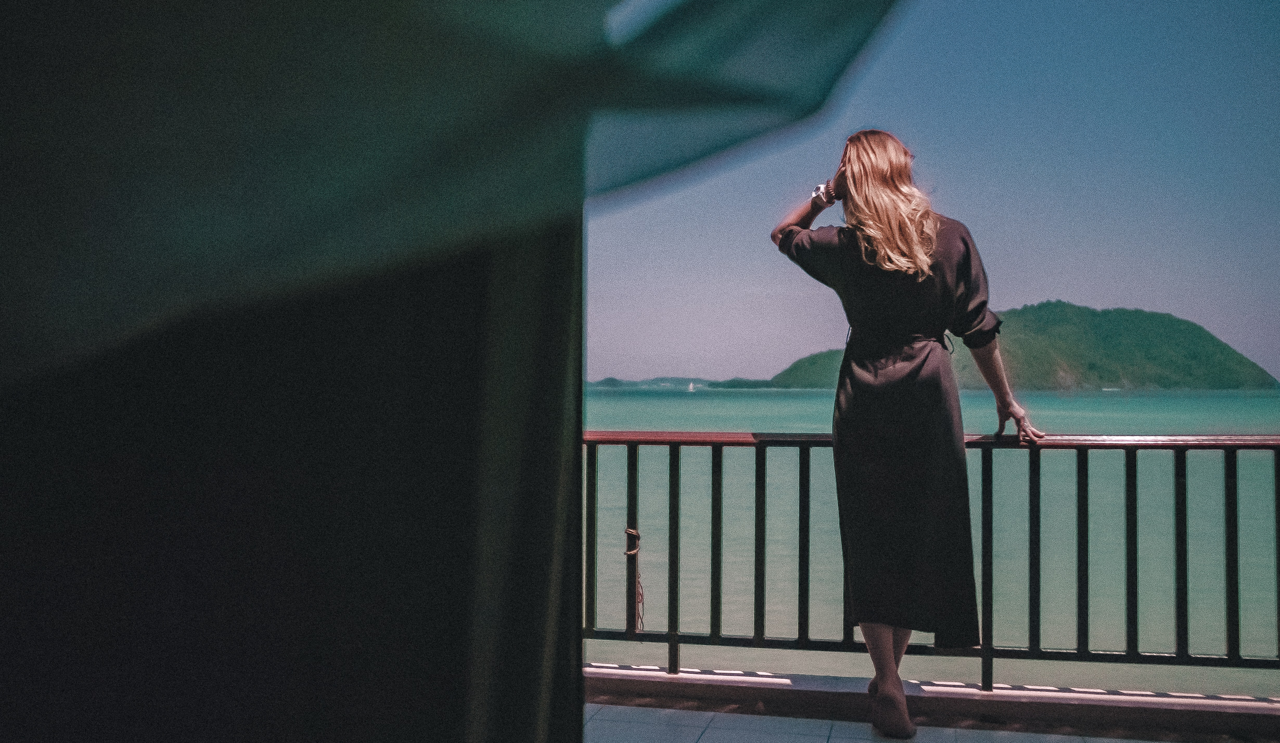 woman in brown robe stands in porch overlooking sea