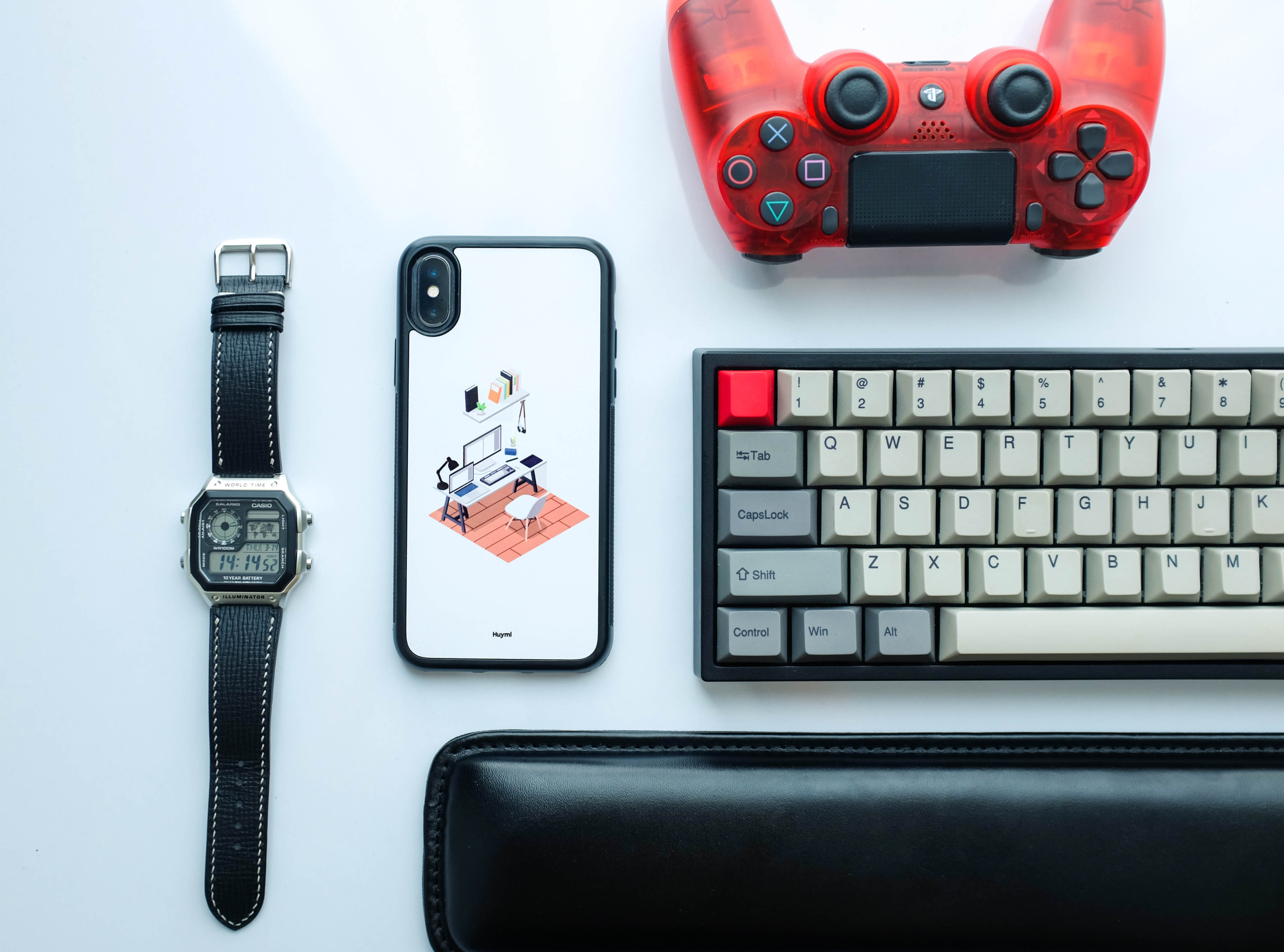 white and black iPhone X case beside silver-colored digital watch