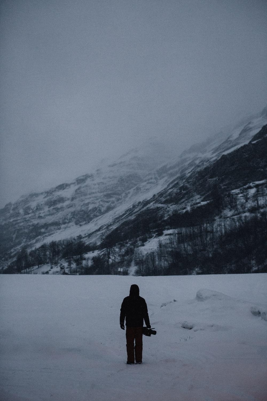 man carrying case near the mountain
