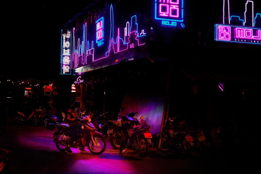 motorcycles park under blue and pink LED signage