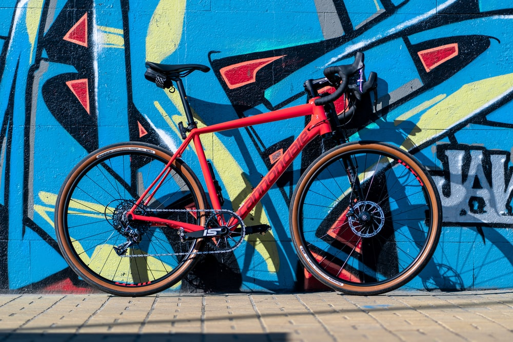 red and black road bike parked beside blue wall