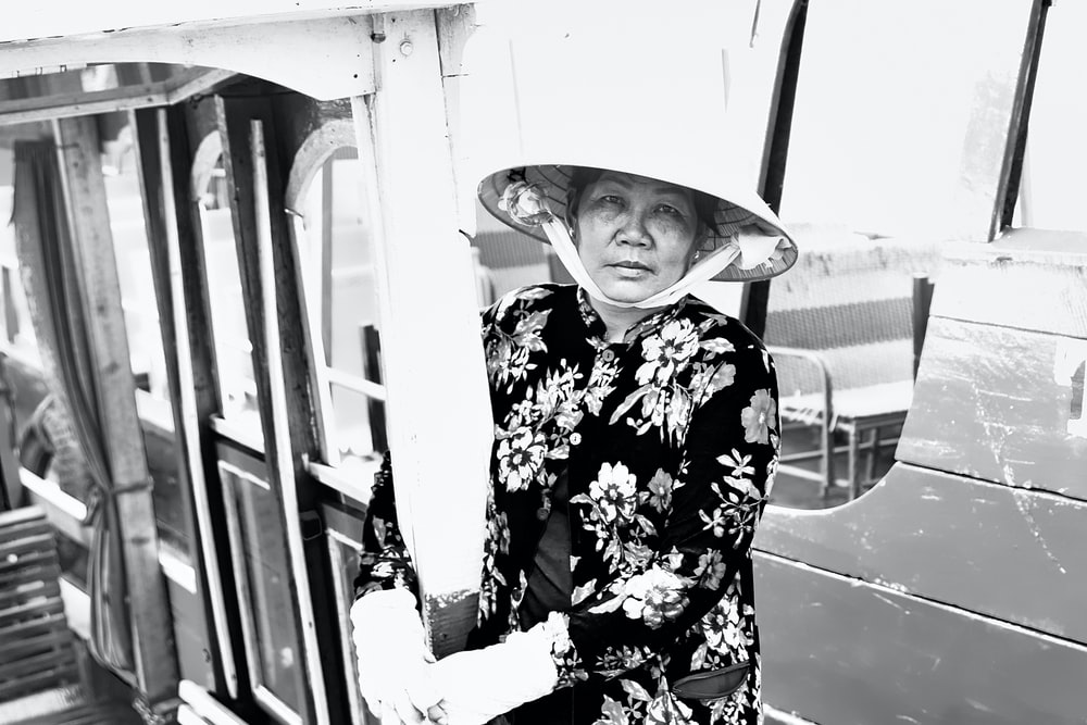 greyscale photo of woman wearing straw hat