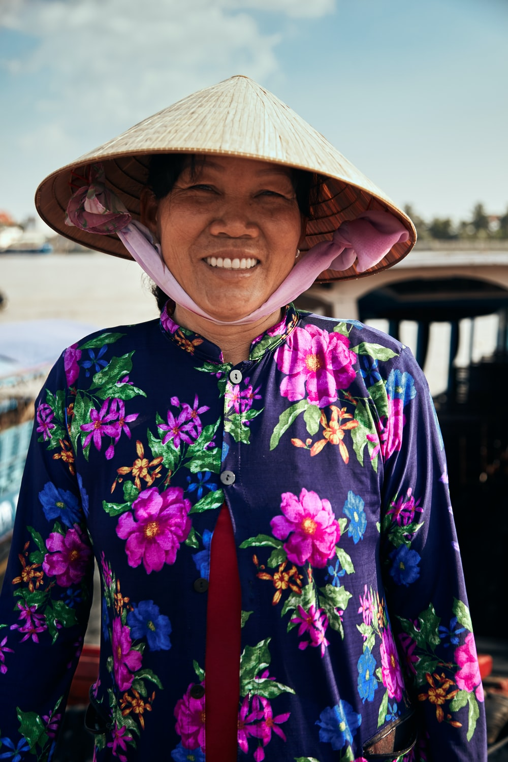 woman in woven hat and floral button-up long-sleeved shirt