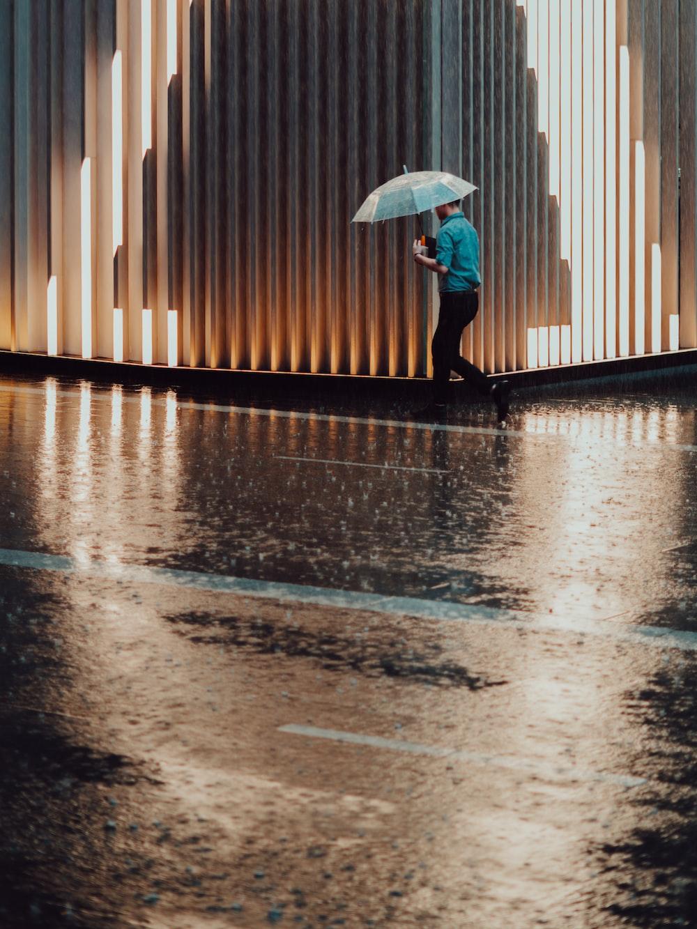 man holding umbrella while walking beside street