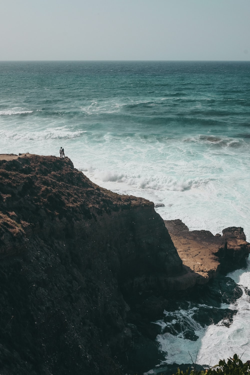 people standing on cliff during daytime