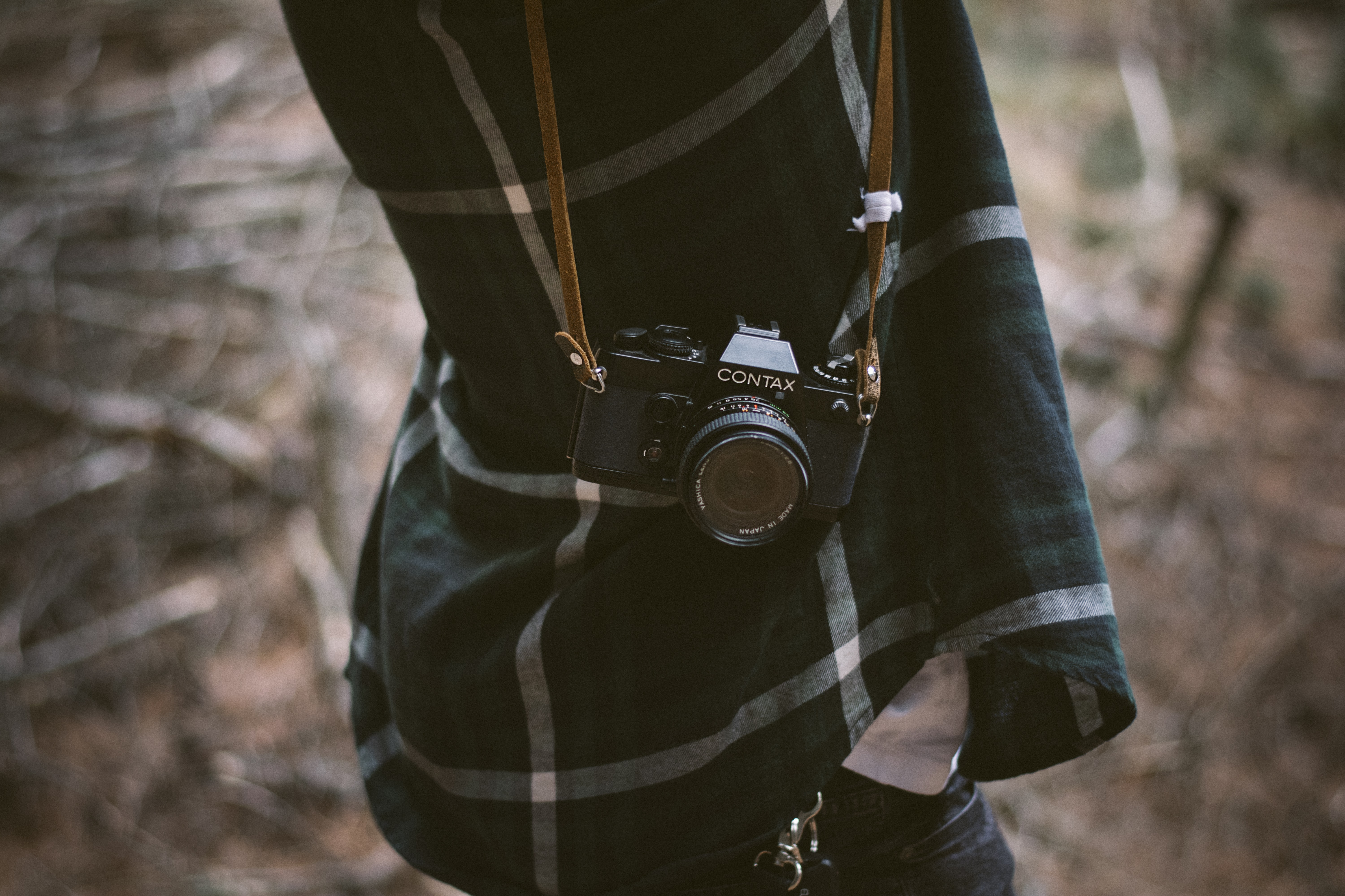 person carrying black Contax mirrorless camera