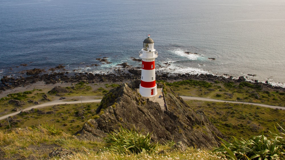 white and red concrete lighthouse