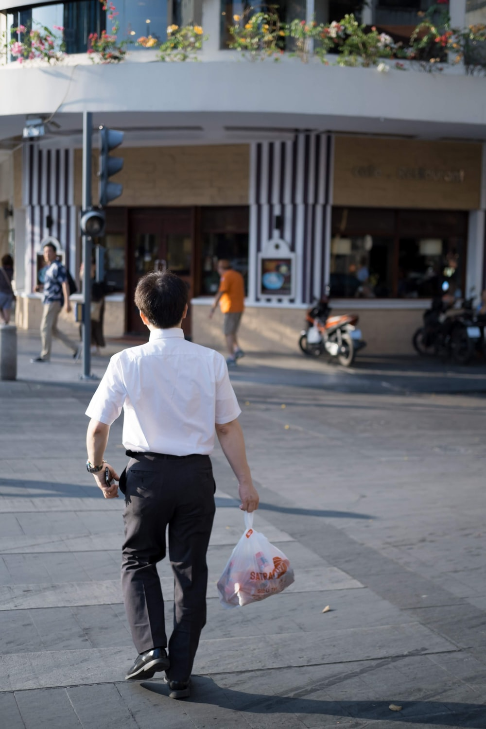 man holding plastic bag while walking at middle of street
