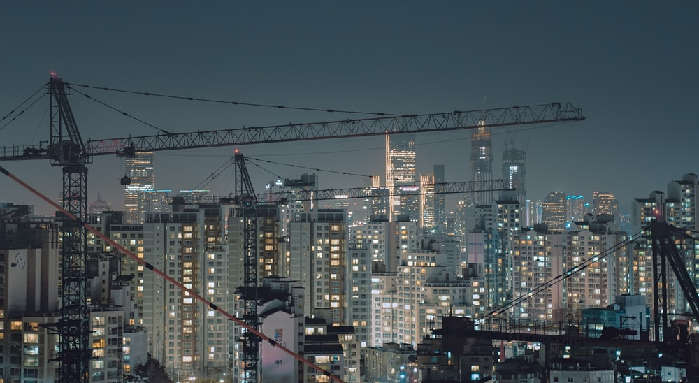 aerial photography of crane overlooking city buildings at night time