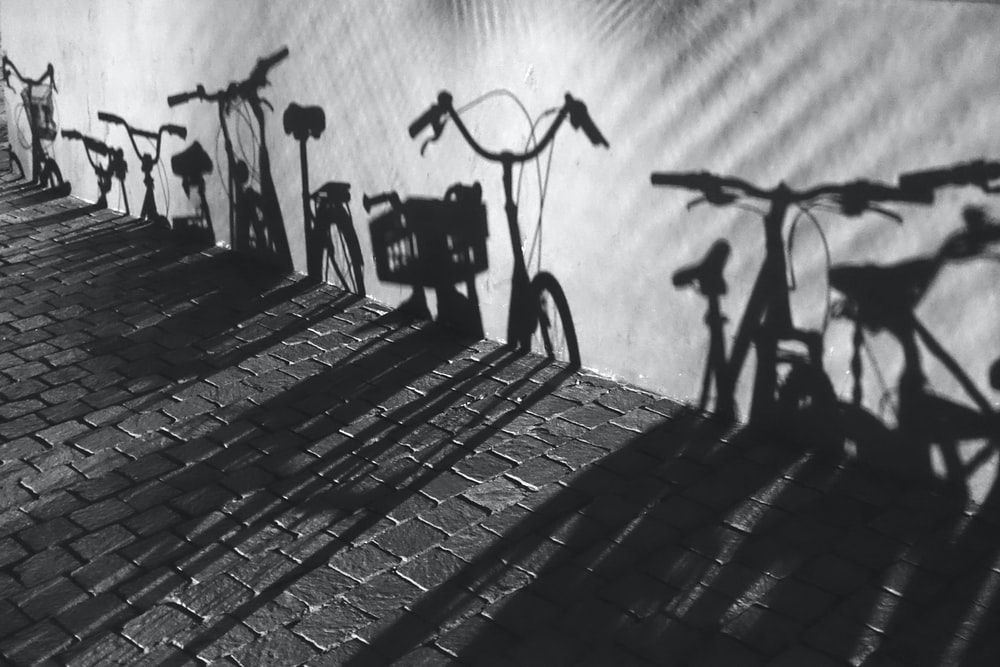 silhouette of bikes on concrete wall in grayscale photography