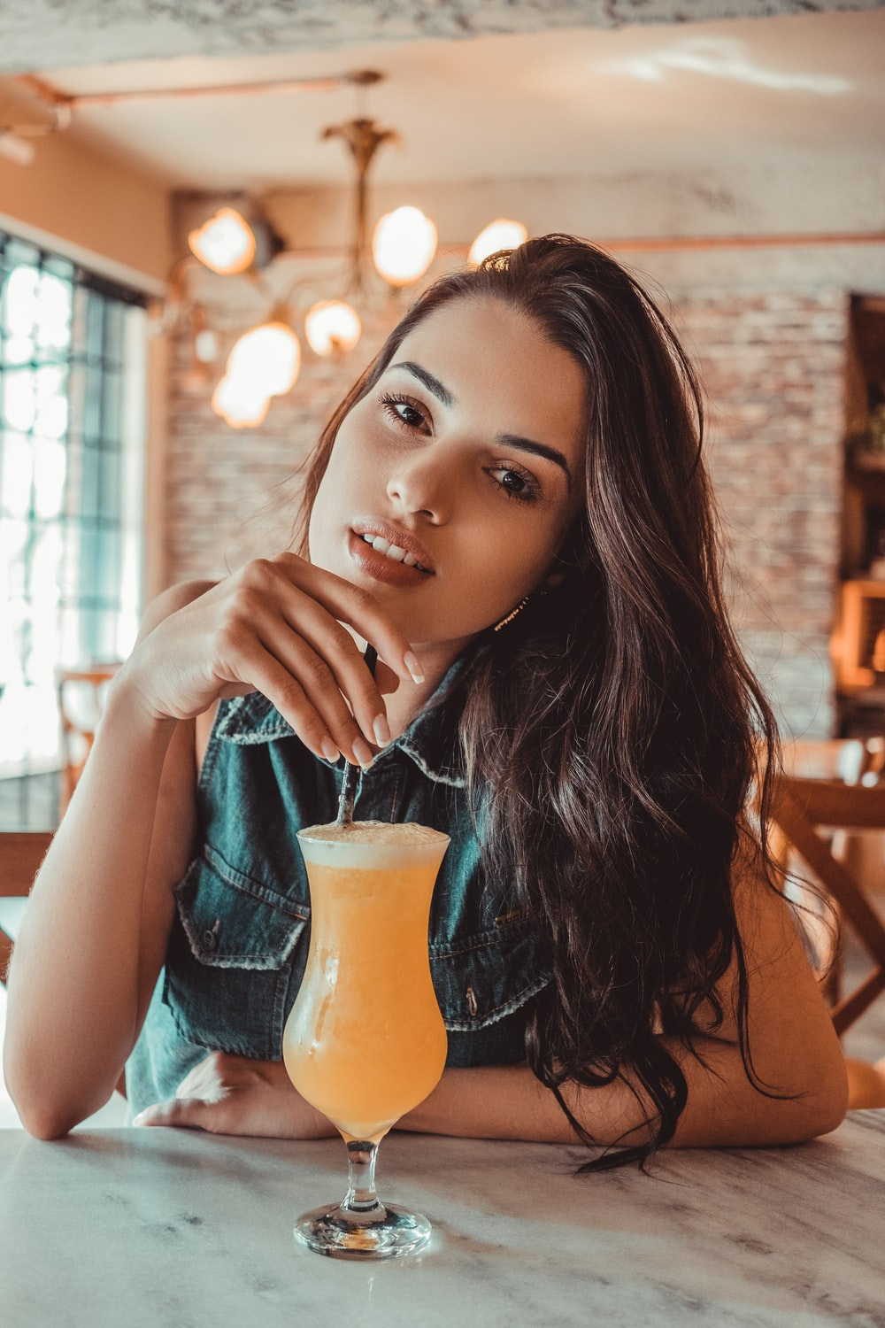 smiling woman sitting near table holding straw