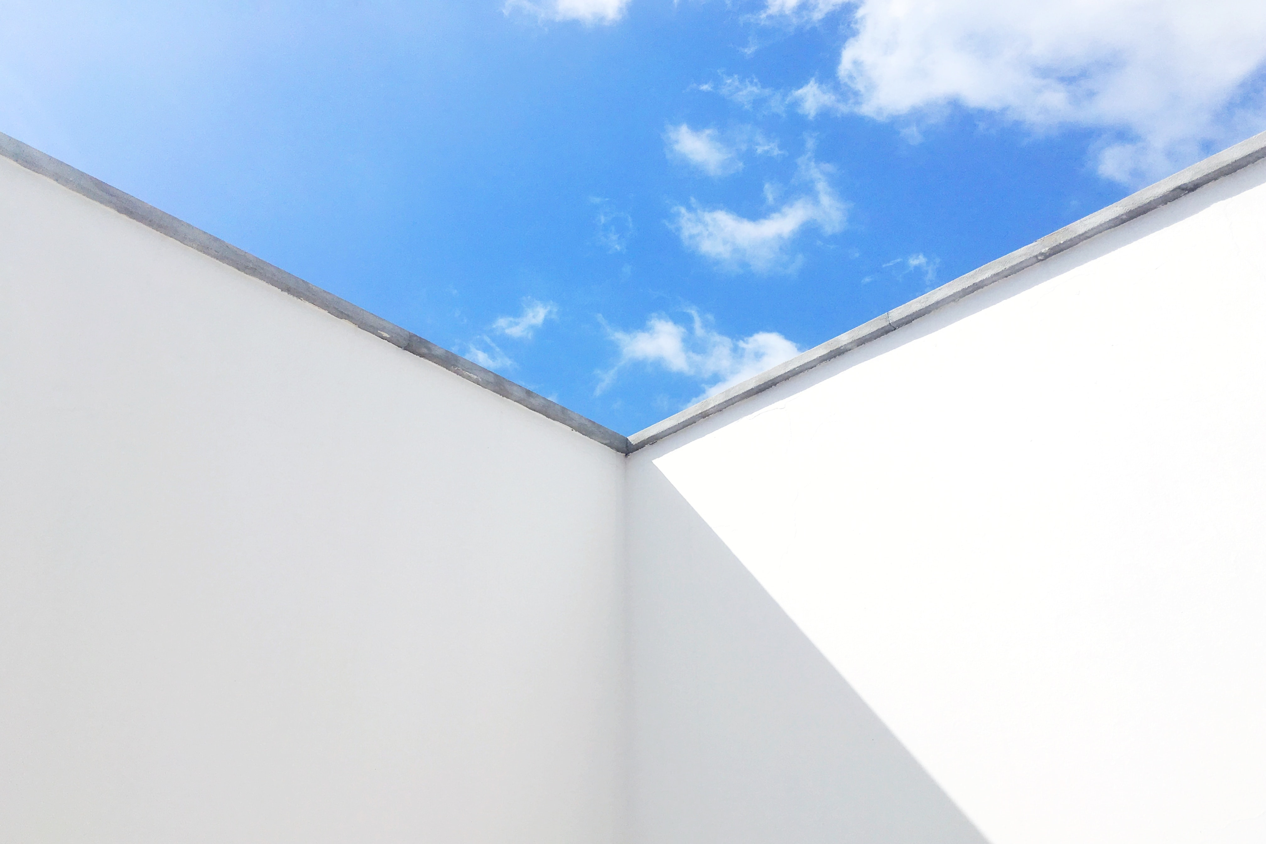 white painted wall under blue and white skies