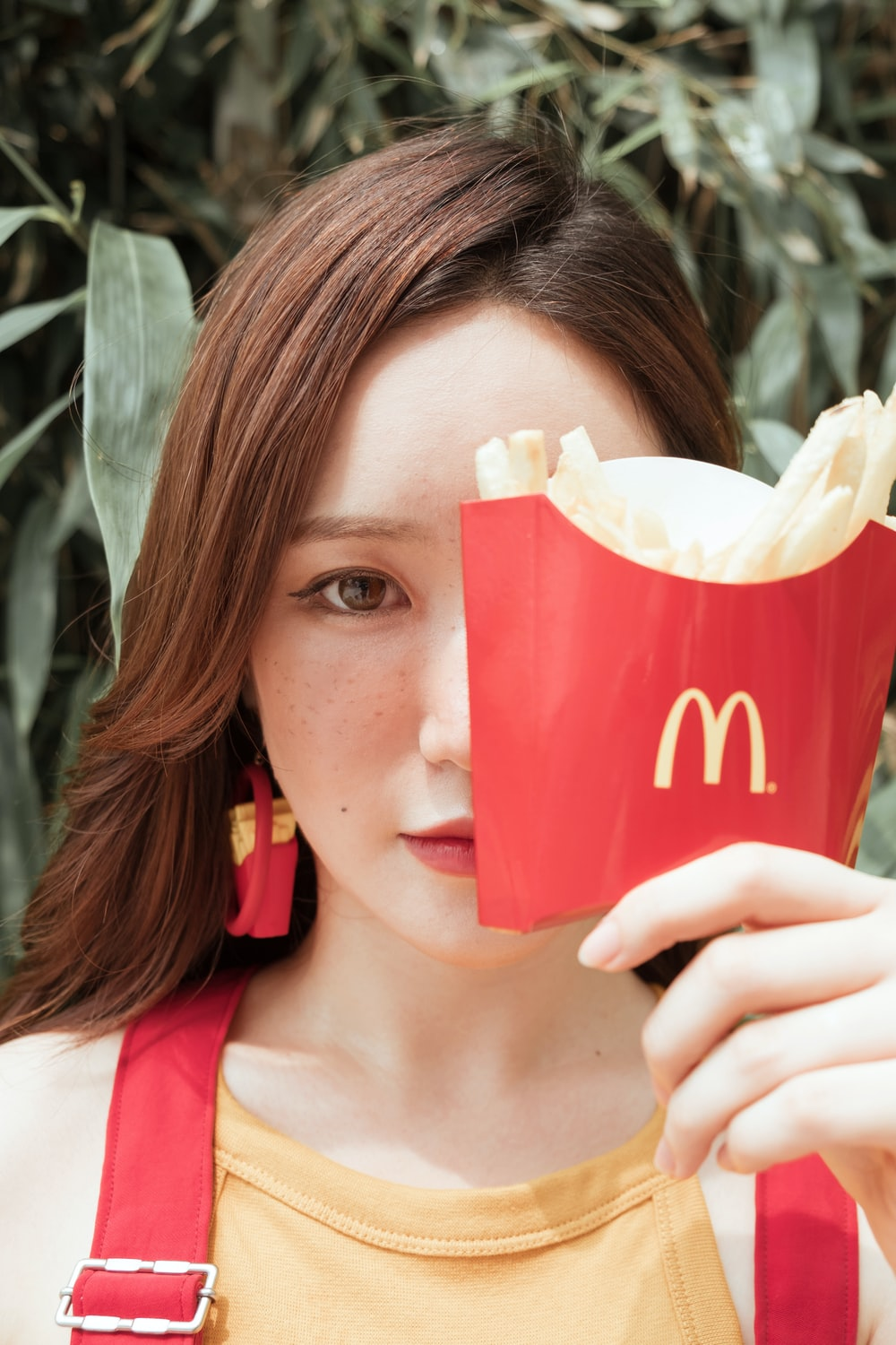 woman holding McDonnalds french fries near face