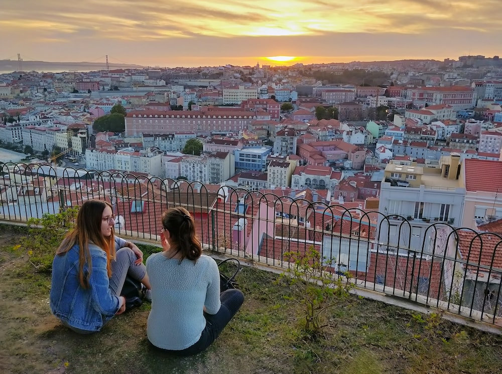 two women sitting on grass near railing with overlooking city under orange sky