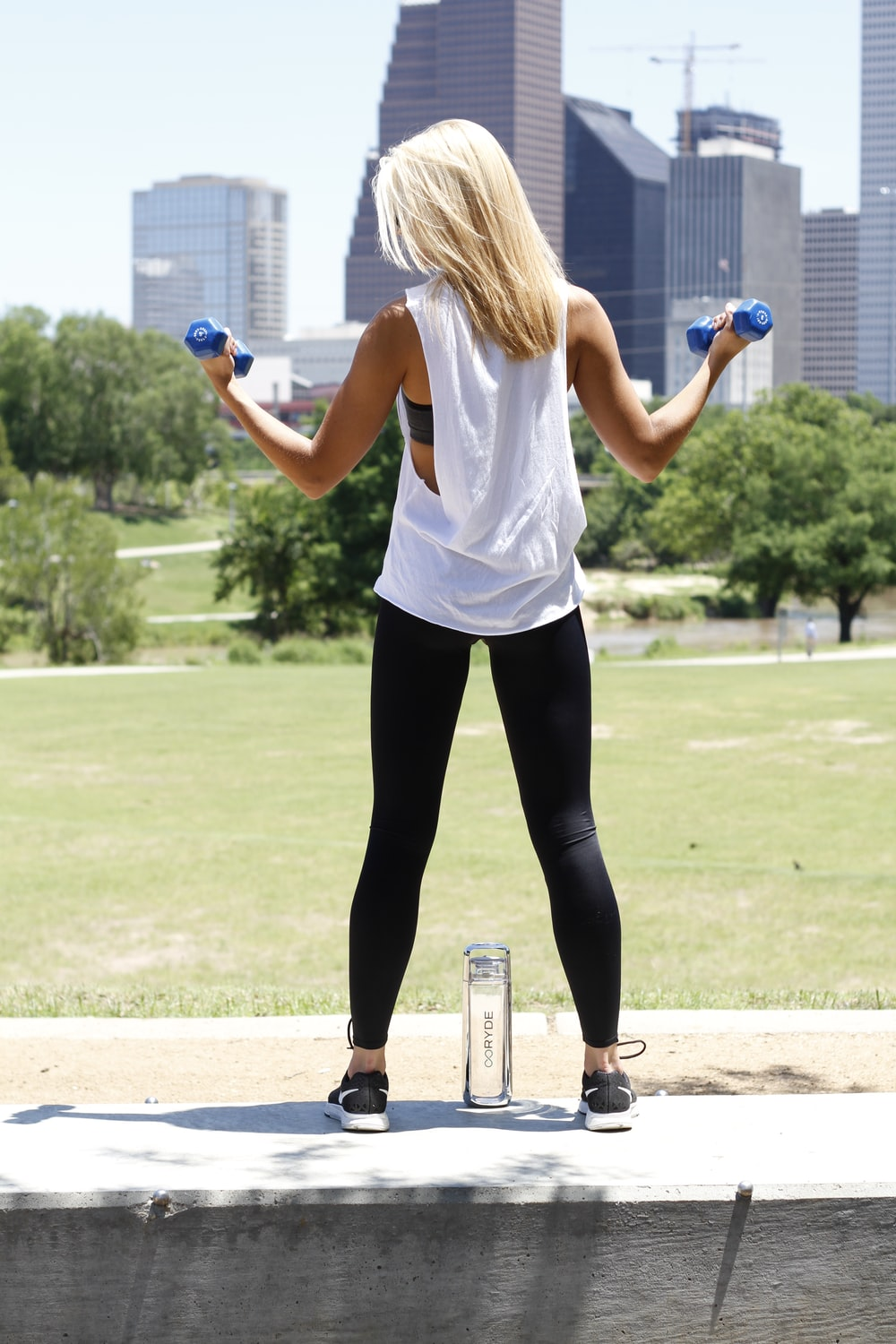 woman carrying blue dumbbells