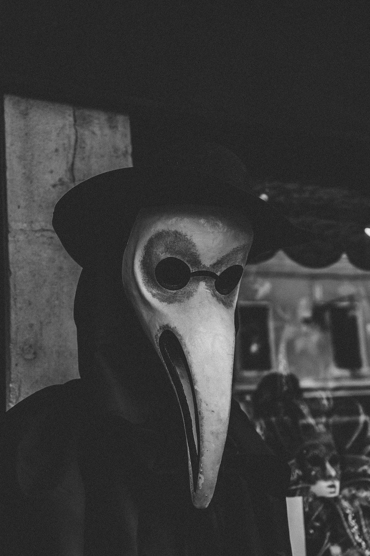 grayscale photo of man wearing gray mask