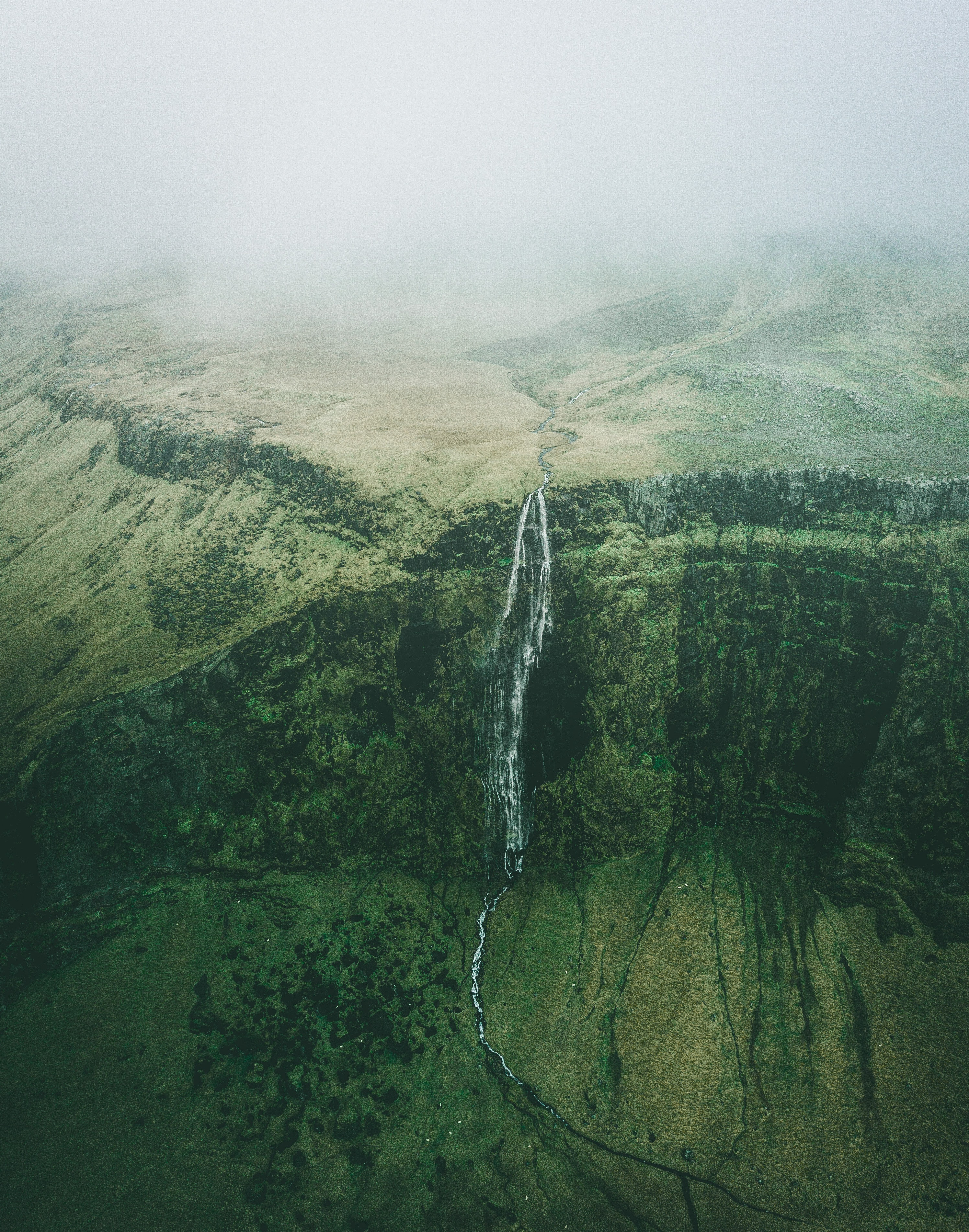 aerial photo of waterfalls during foggy weather