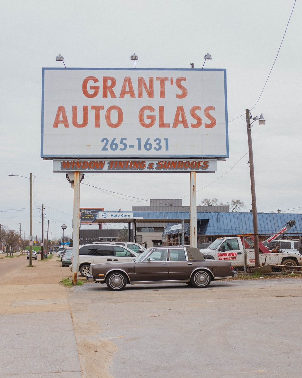 cars parked near Grant's auto Glass signage