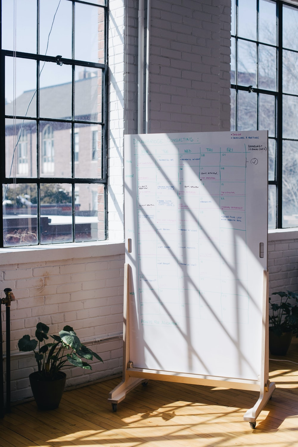 white wooden board near window and plant