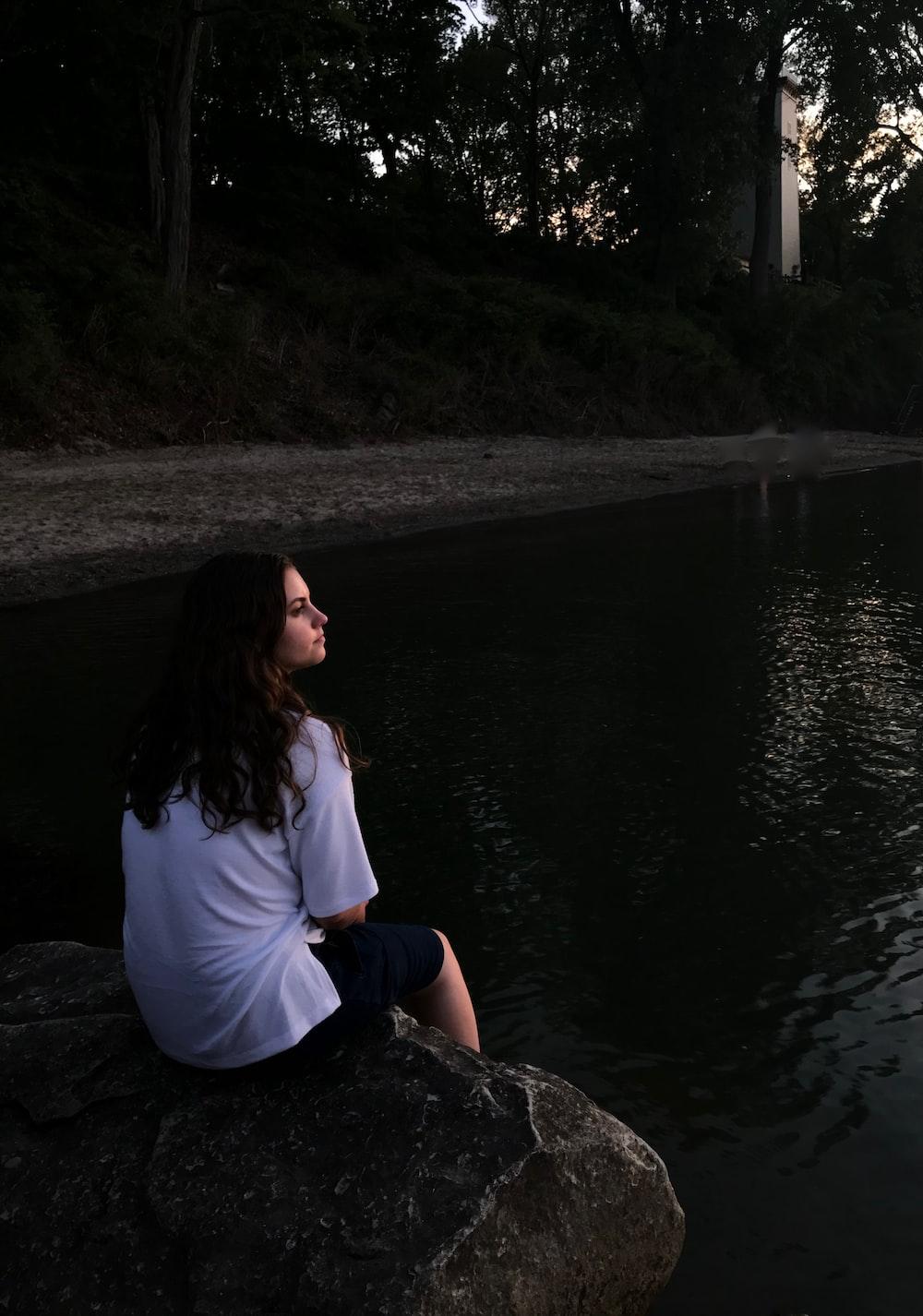 woman sitting on rock while facing lake