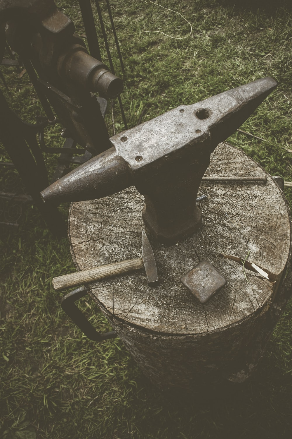 metal anvil on cut log with hammers