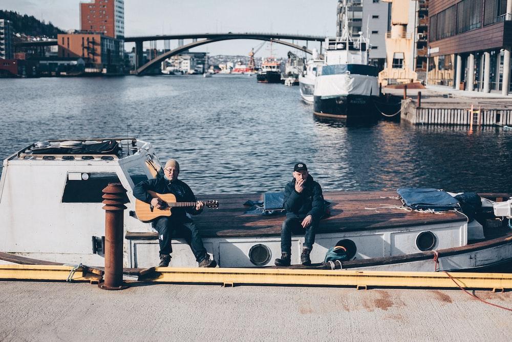 men sitting while playing guitar on boat at dock during daytime