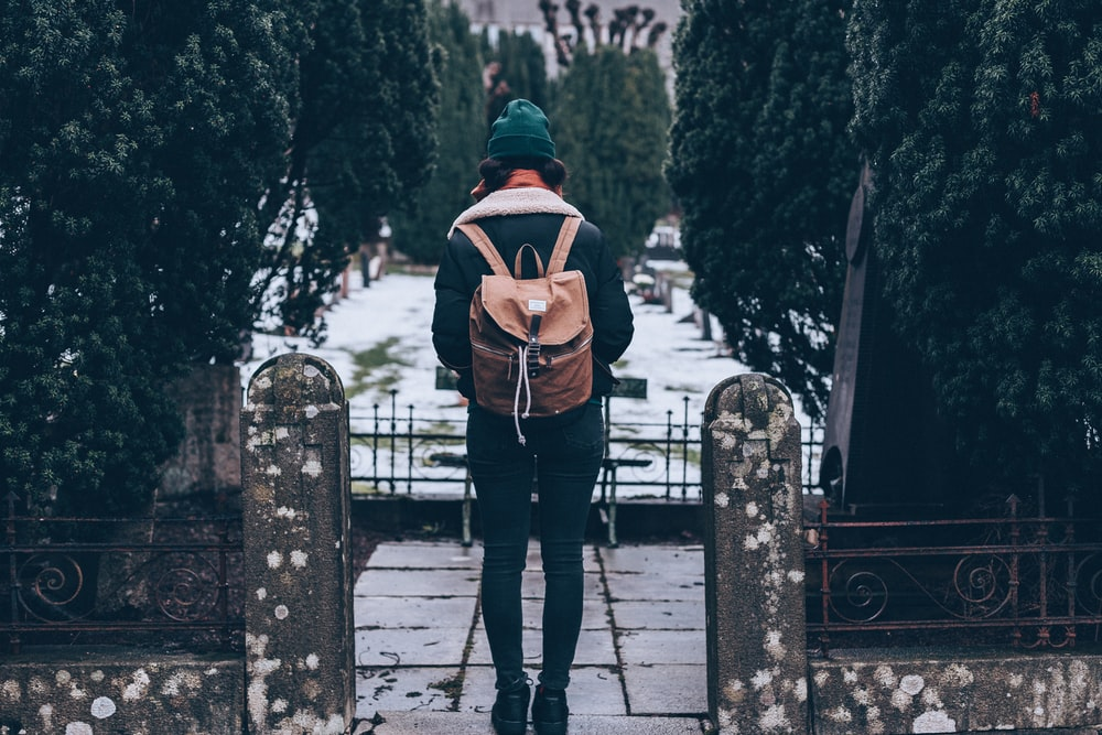 woman standing on pathway carrying backpack