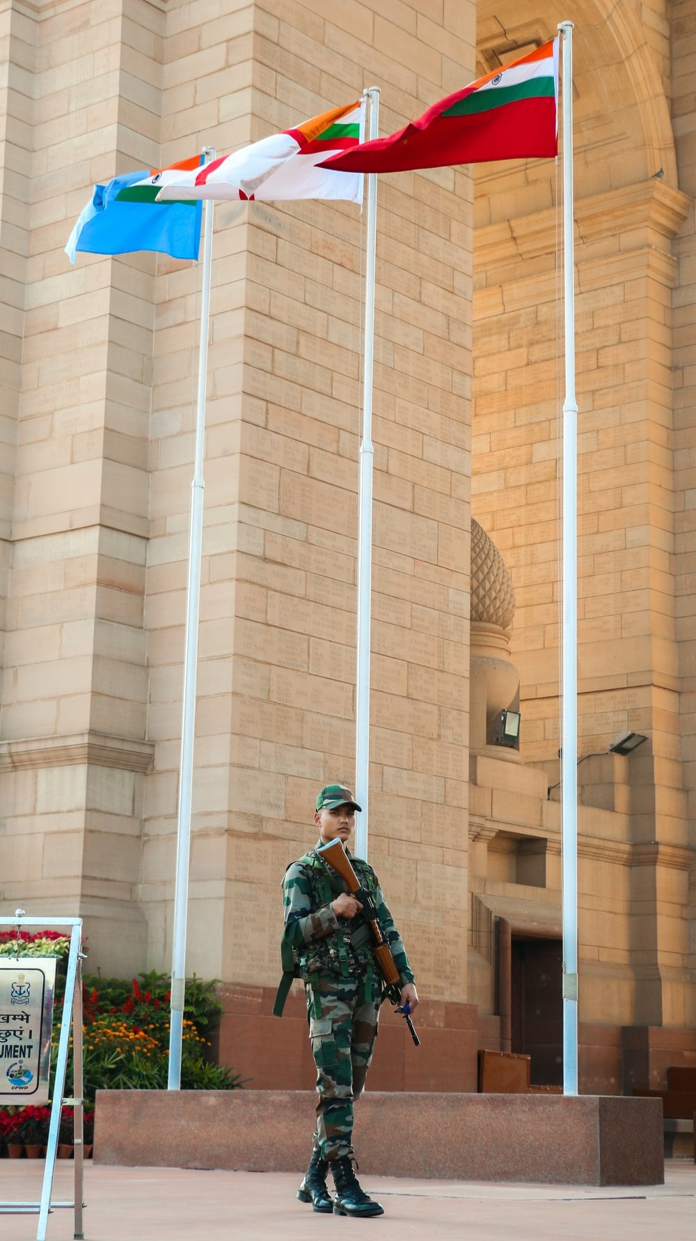 soldier standing beside flags