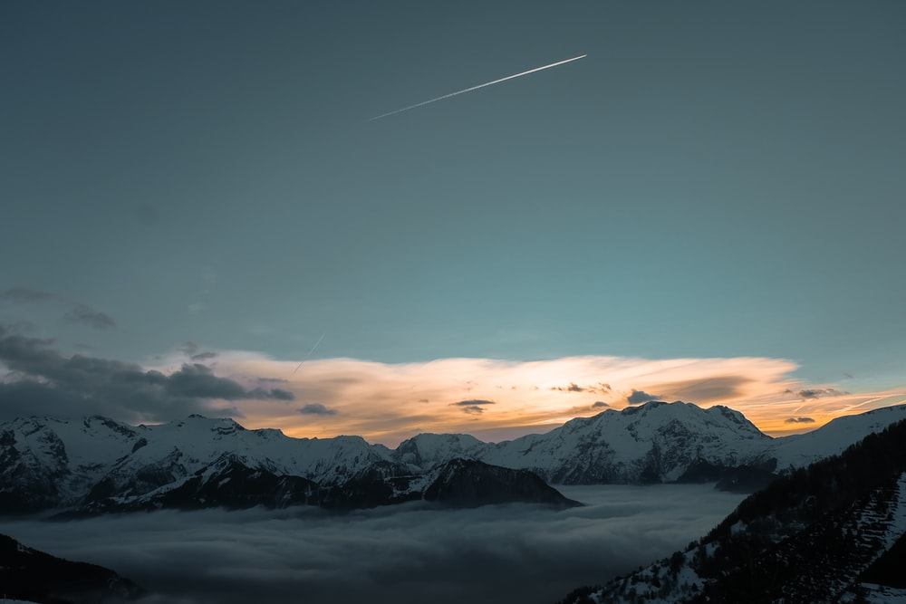 shooting star above snow-capped mountains during golden hour