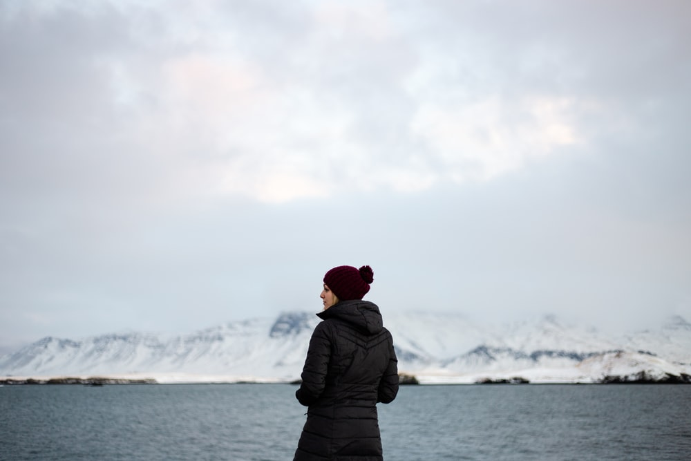 woman wearing winter coat near the sea