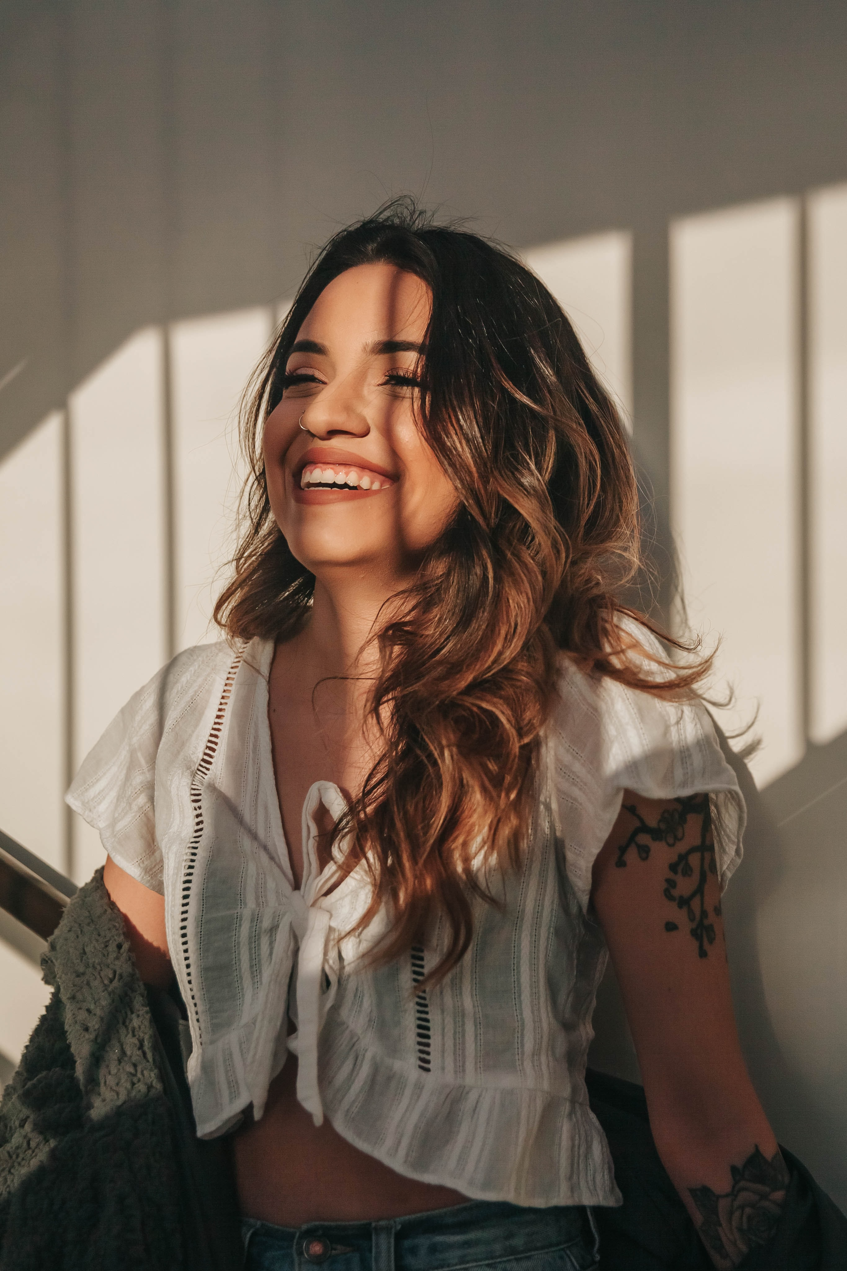 woman in white top smiling while leaning on white wall