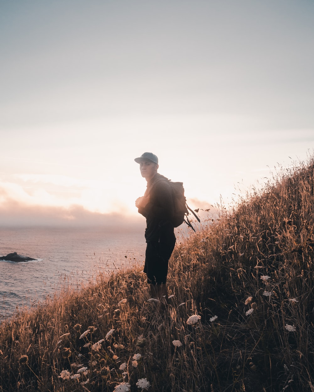 man with backpack standing at the hill overlooking the ocean
