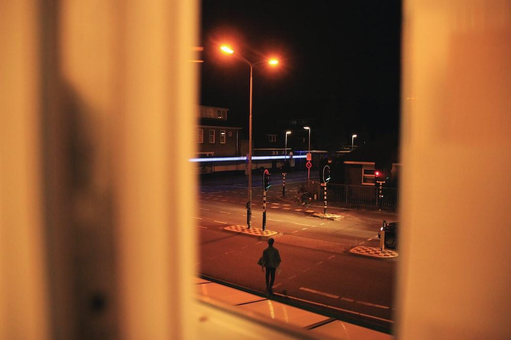 man walking on road during nighttime