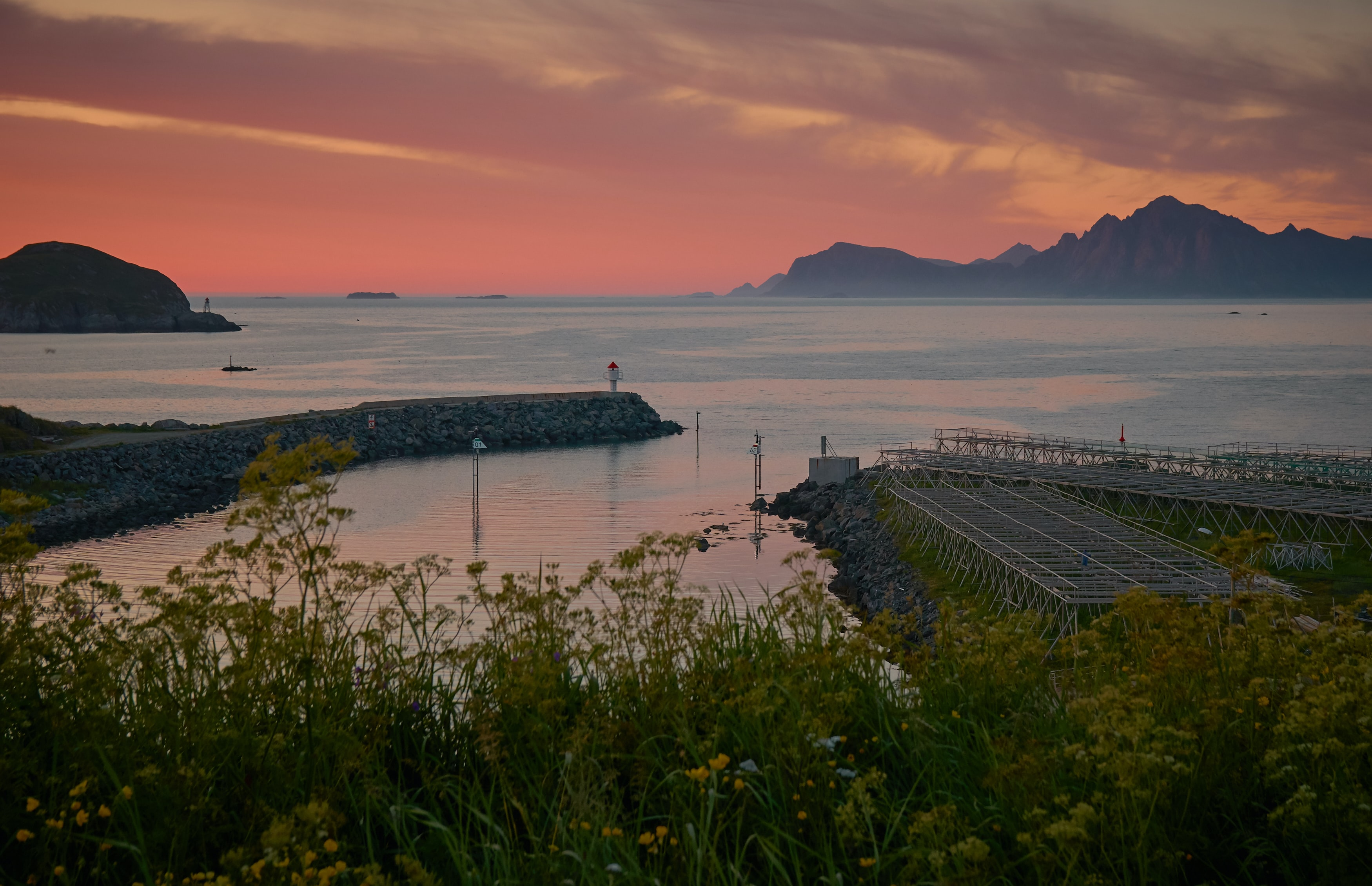 calm sea beside mountain and docks during golden hour