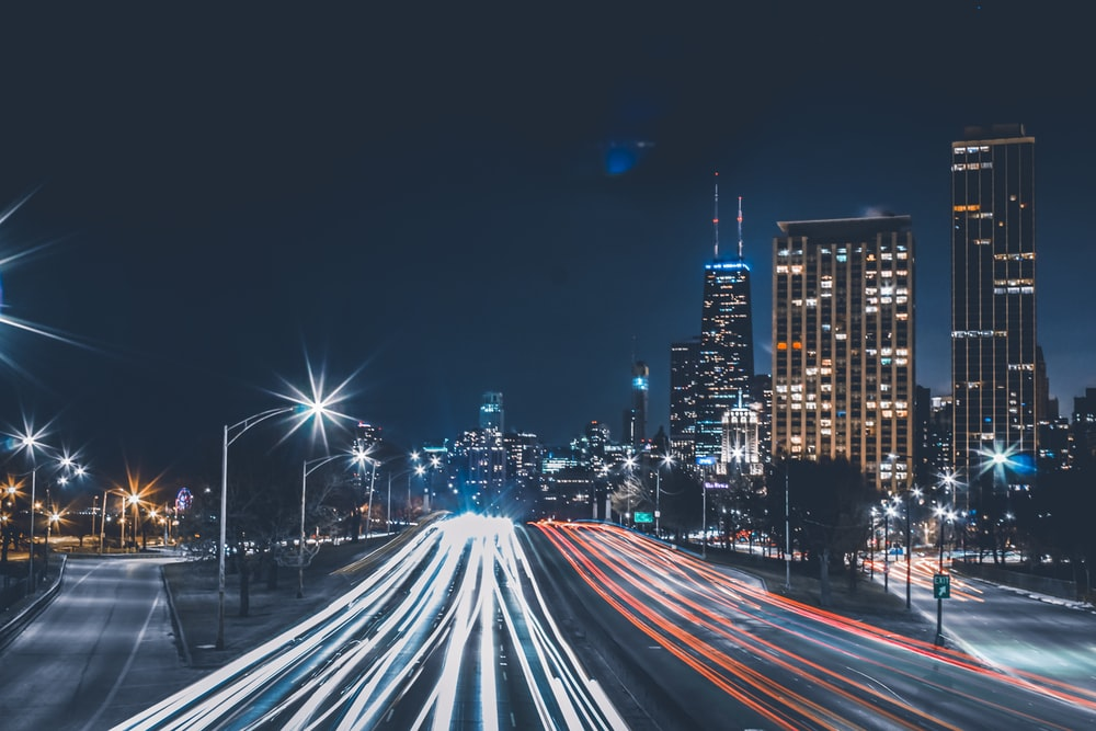 timelapse photography of vehicle taillights on road with high-rise buildings