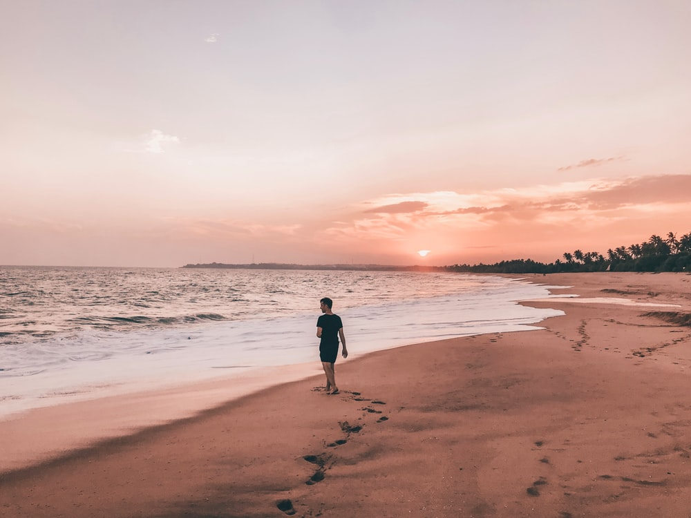 man in black in beach at sunset