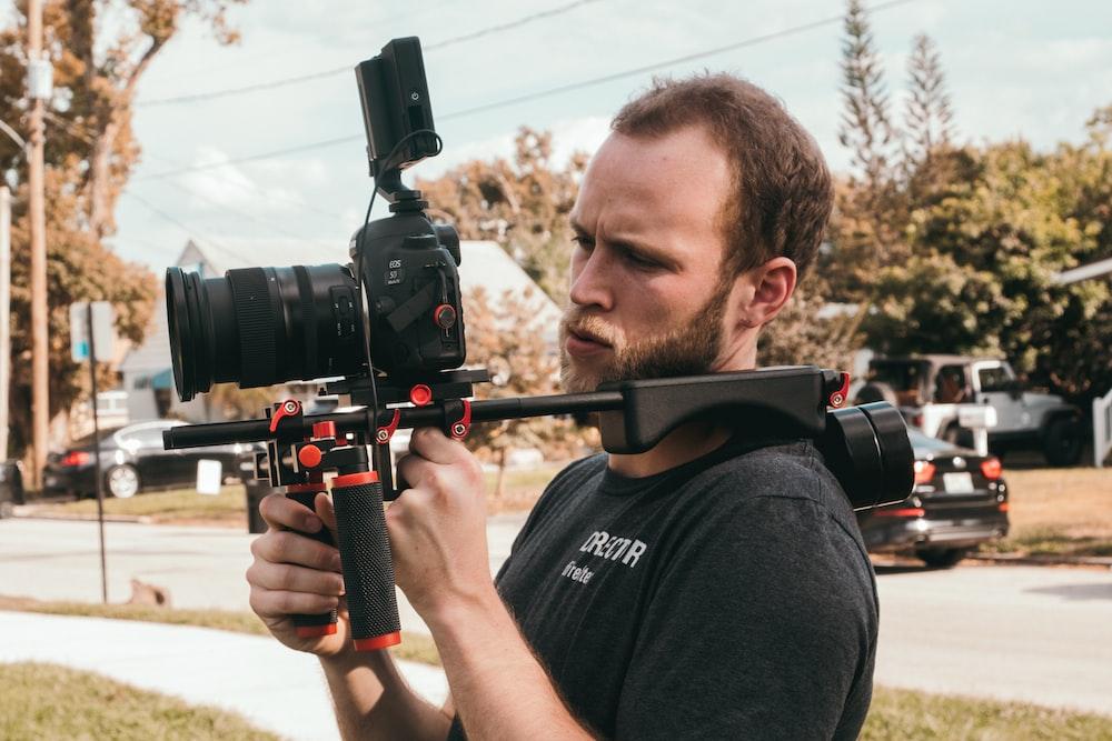 man holding camera during daytime