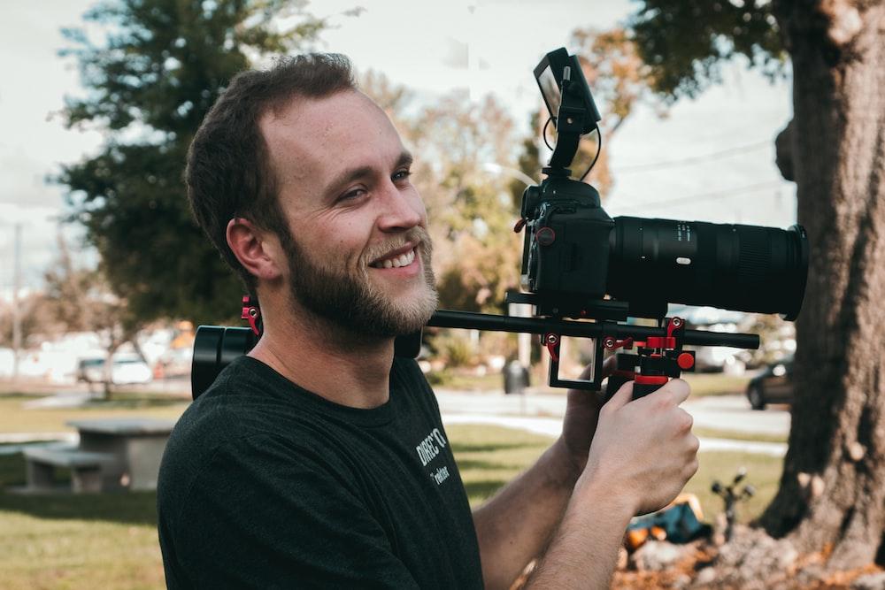 man smiling standing near the DSLR camera