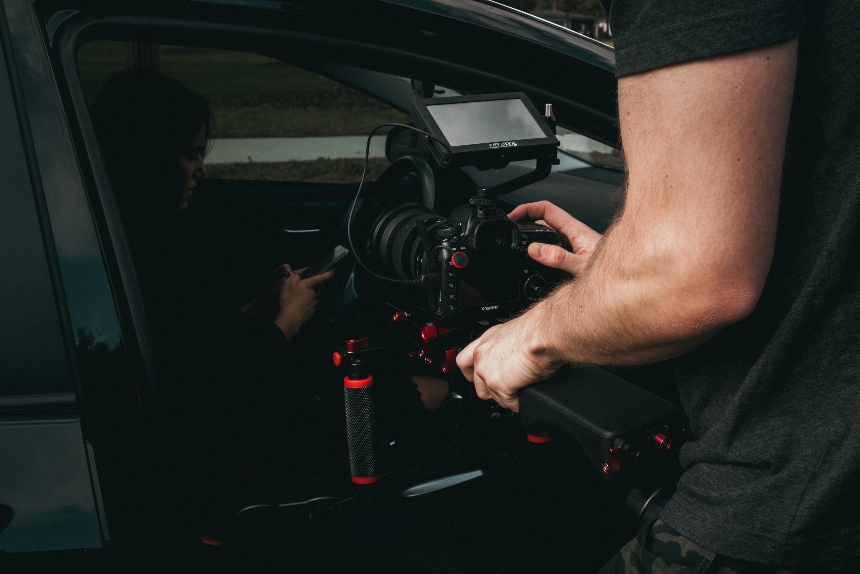 man taking video of woman inside vehicle