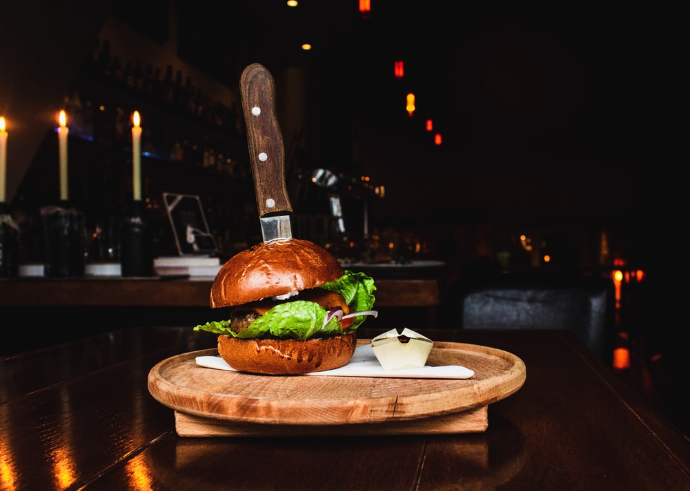 selective focus photography of burger on brown wooden tray
