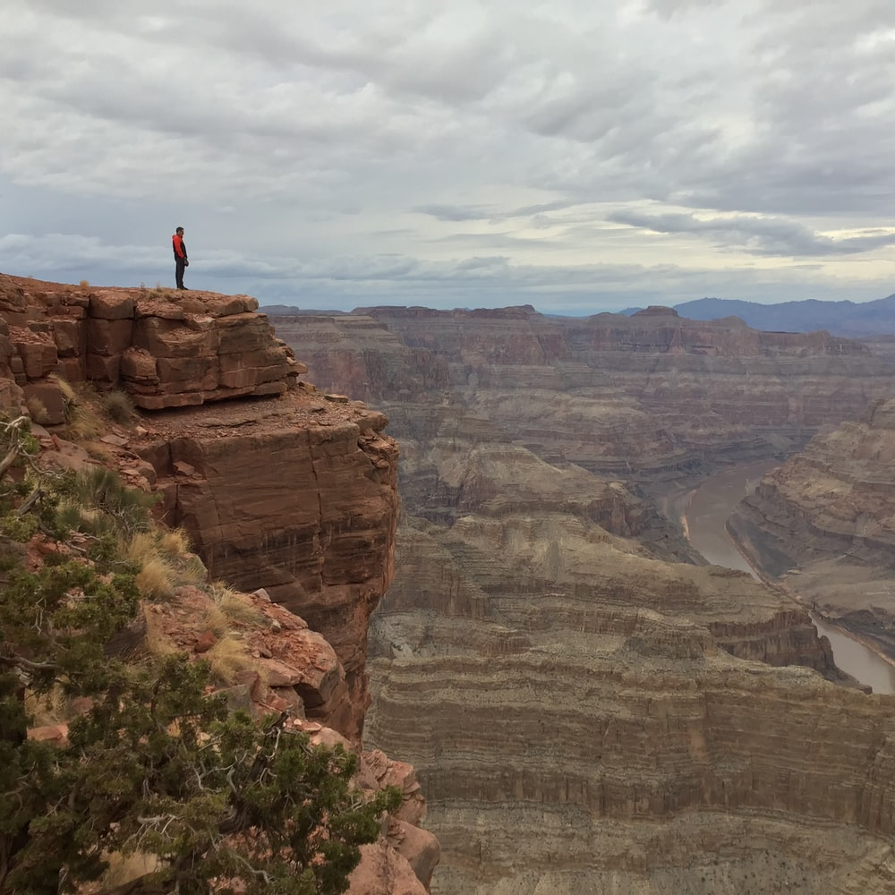 person standing near edge of rocky mountain