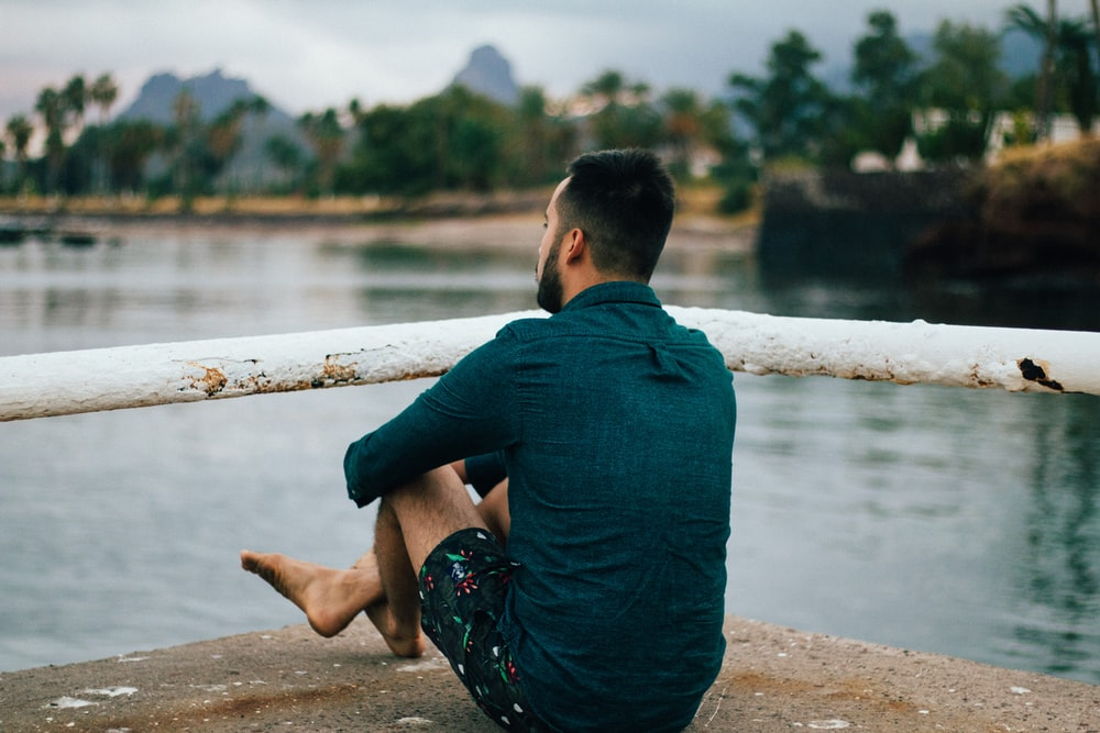 man sitting near metal bar in front of body of water