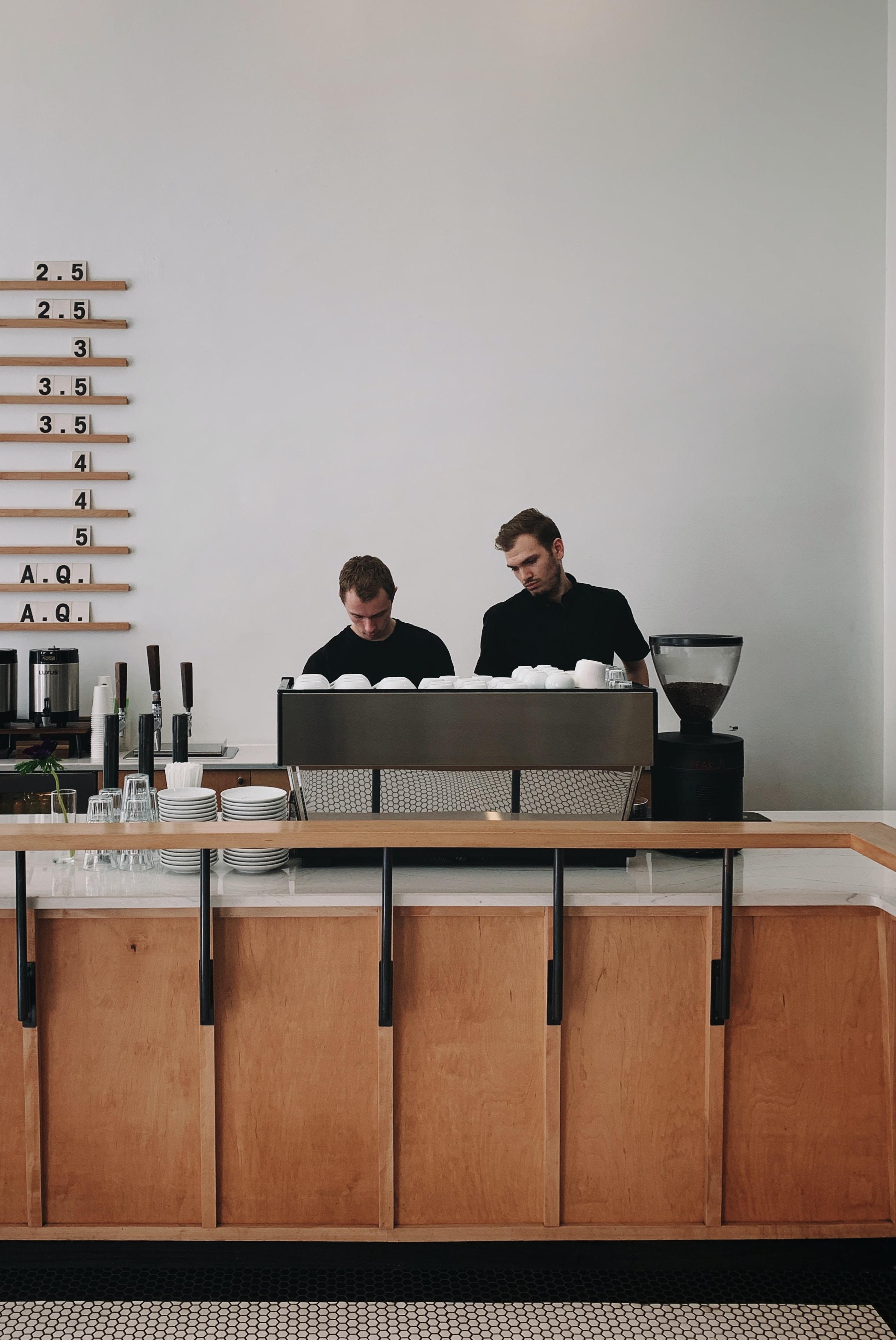 two men standing near sectional desk