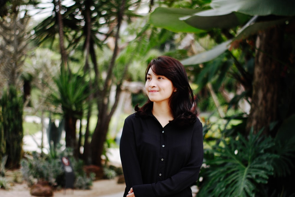 woman in black dress shirt standing near trees and smiling